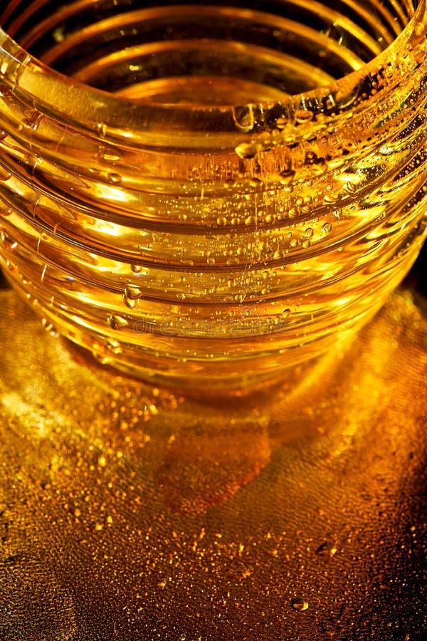 Χρυσή σύσταση με τις πτώσεις νερού Δίψα και η απόσβεσή του Πτώσεις του μελιού στο γυαλί στοκ εικόνα με δικαίωμα ελεύθερης χρήσης