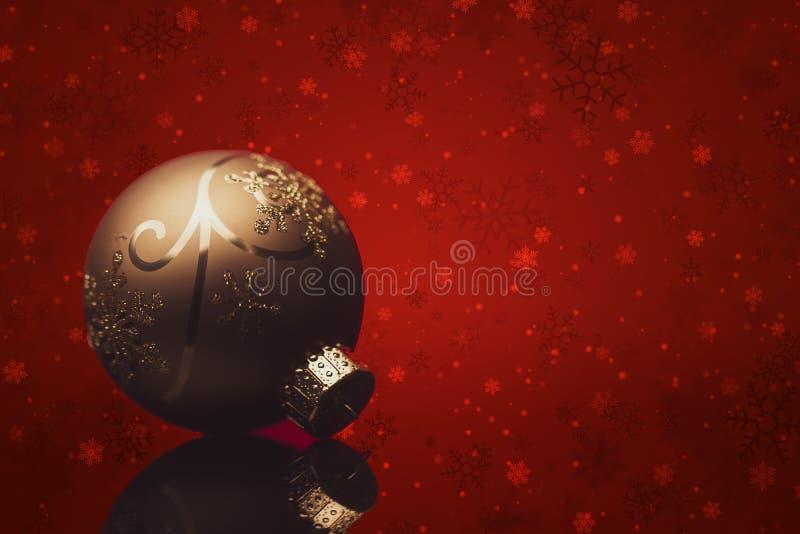 Χρυσή χριστουγεννιάτικη μπάλα σε κόκκινο φόντο στοκ εικόνα με δικαίωμα ελεύθερης χρήσης