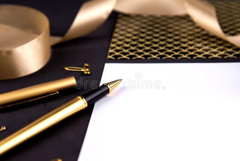 Χρυσοί μάνδρα, κορδέλλα, συνδετήρες εγγράφου και χαρτικά σε ένα μαύρο υπόβαθρο με ένα άσπρο φύλλο του εγγράφου με το διάστημα αντ στοκ φωτογραφίες