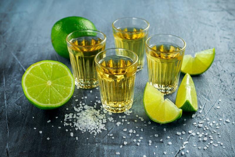 Χρυσοί πυροβολισμοί Tequila με το άλας ασβέστη και θάλασσας στοκ εικόνες