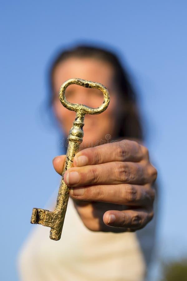 Χρυσός βασικός διαθέσιμος μπλε ουρανός χεριών γυναικών στοκ φωτογραφία