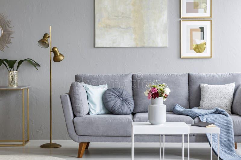 Χρυσός λαμπτήρας δίπλα στον γκρίζο καναπέ στο σύγχρονο εσωτερικό καθιστικών με στοκ εικόνα με δικαίωμα ελεύθερης χρήσης