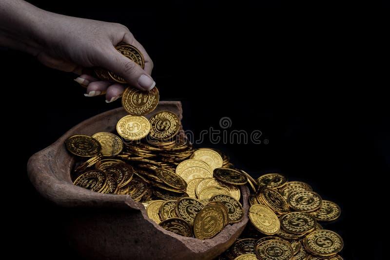 Χρυσός νομισμάτων στο γυναικείο χέρι στα μέρη που συσσωρεύουν τα χρυσά νομίσματα στο σπασμένο άσπρο υπόβαθρο βάζων, σωρός χρημάτω στοκ φωτογραφία