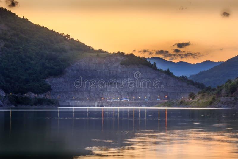 Χρυσός, ουρανός ηλιοβασιλέματος με τα χνουδωτά σύννεφα πέρα από την αντανακλαστική, μεταξωτή λίμνη στοκ εικόνες