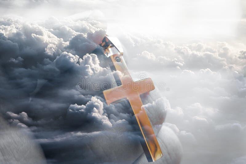 Χρυσός σταυρός του Ιησούς Χριστού υπό εξέταση με τα σύννεφα στο υπόβαθρο στοκ εικόνες