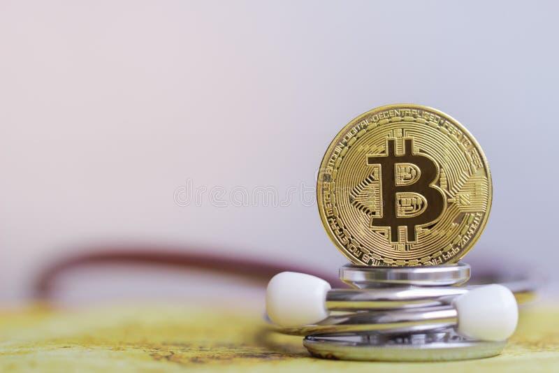 Χρυσός bitcoin με τον έλεγχο στηθοσκοπίων επάνω στην άσπρη υγειονομική περίθαλψη υποβάθρου στοκ εικόνα