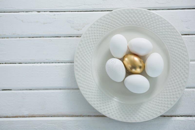 Χρυσό αυγό Πάσχας με τα άσπρα αυγά στο πιάτο στοκ εικόνα