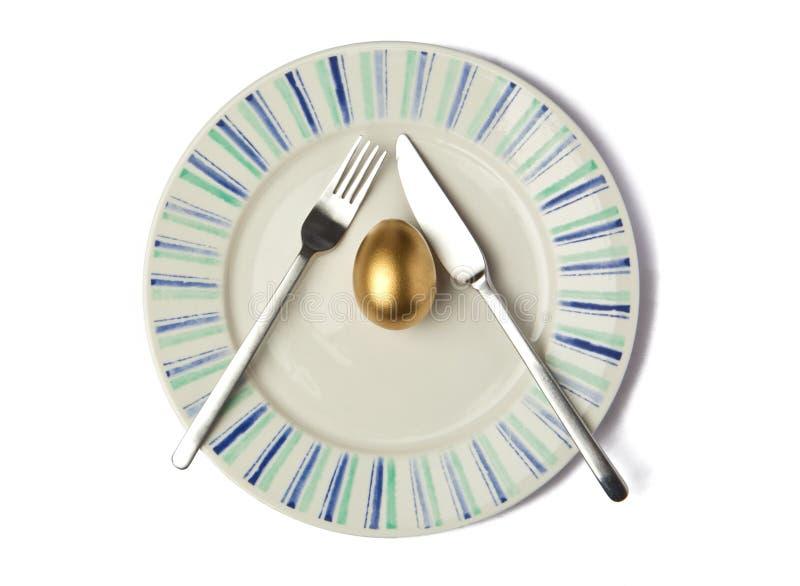 Χρυσό αυγό στο πιάτο στοκ εικόνα με δικαίωμα ελεύθερης χρήσης