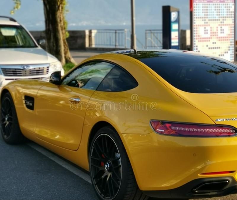 Χρυσό αυτοκίνητο πολυτέλειας πέρα από ένα χρυσό φως κοντά στην ακτή της λίμνης Γενεύη στοκ εικόνες