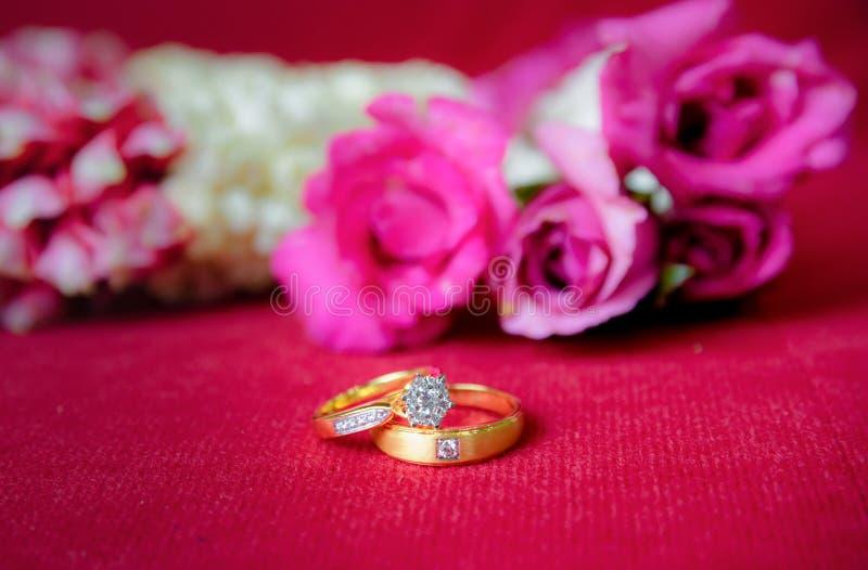 Χρυσό γαμήλιο δαχτυλίδι και κόκκινα τριαντάφυλλα στοκ φωτογραφίες