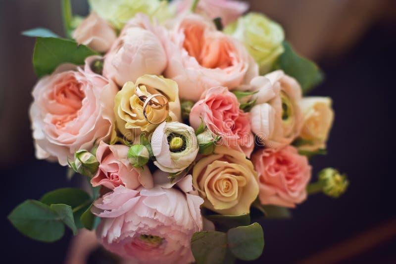 Χρυσό γαμήλιο δαχτυλίδι στην ανθοδέσμη της νύφης στοκ φωτογραφία