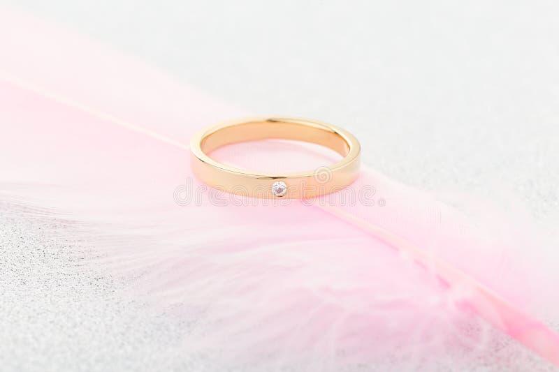 Χρυσό δαχτυλίδι δέσμευσης με ένα διαμάντι στο ρόδινο φτερό στοκ φωτογραφία