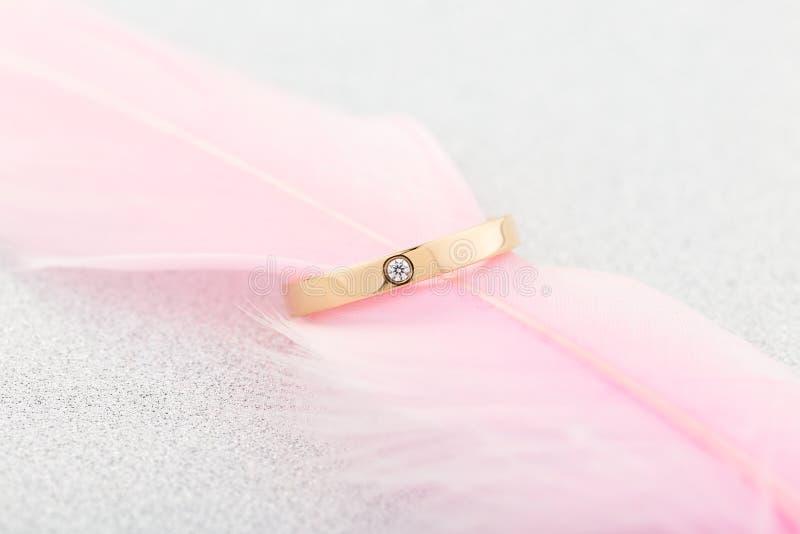 Χρυσό δαχτυλίδι δέσμευσης με ένα διαμάντι στο ρόδινο φτερό στοκ εικόνες