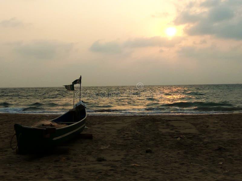 Χρυσό ηλιοβασίλεμα με το αλιευτικό σκάφος στην παραλία θάλασσας στοκ εικόνες