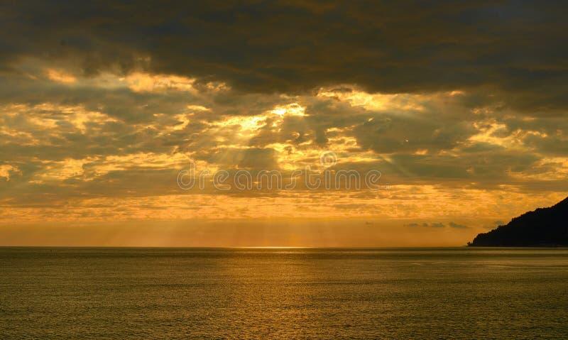 Χρυσό ηλιοβασίλεμα πέρα από τη θάλασσα με τα σύννεφα, βουνό στο backlight στοκ εικόνες