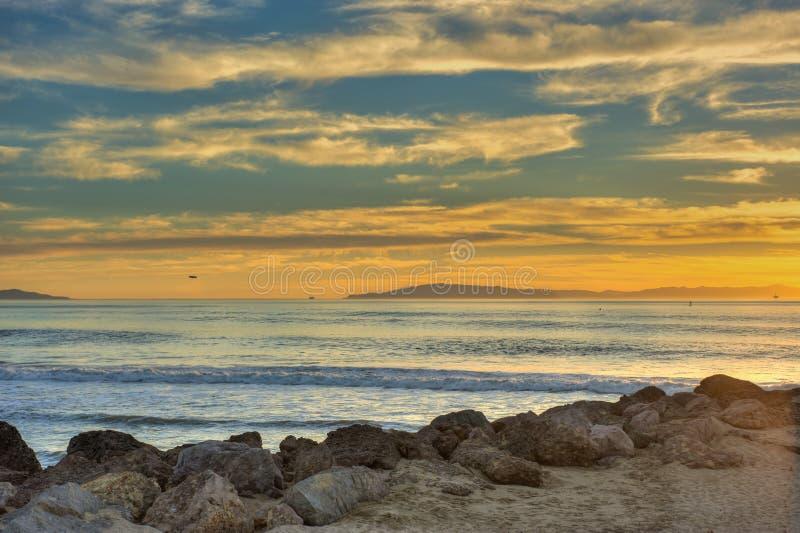 Χρυσό ηλιοβασίλεμα πέρα από το λαμπρό ωκεάνιο νερό στοκ εικόνα