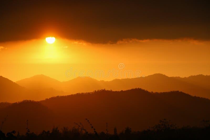 Χρυσό ηλιοβασίλεμα πέρα από το βουνό και το δάσος στοκ φωτογραφίες