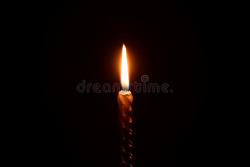 Χρυσό κάψιμο κεριών σε ένα μαύρο υπόβαθρο στοκ φωτογραφίες