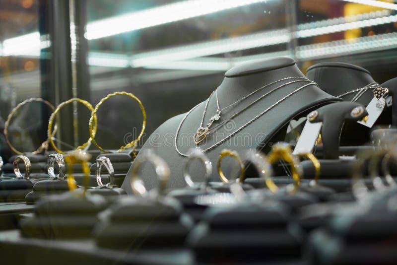 Χρυσό κατάστημα διαμαντιών κοσμήματος με τα δαχτυλίδια και τα περιδέραια μορφής καρδιών στοκ εικόνες