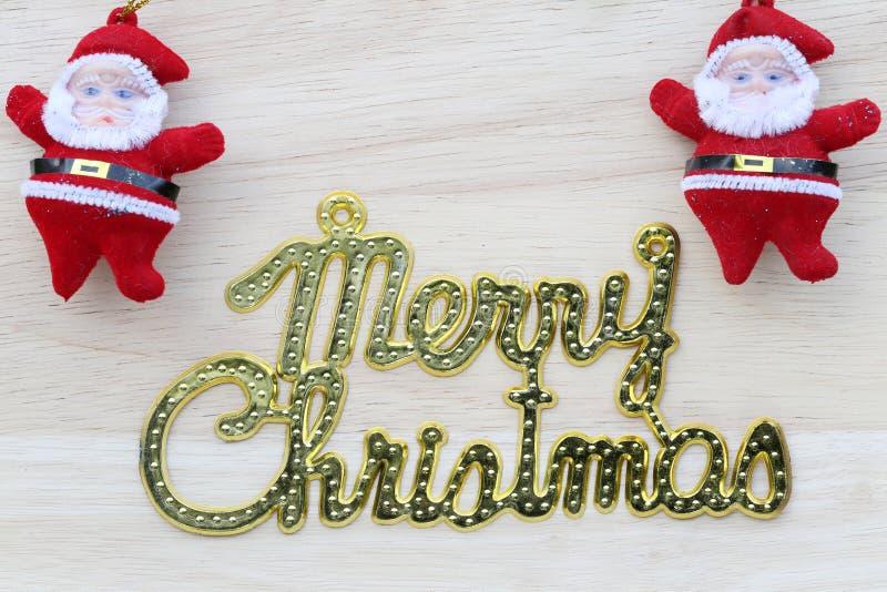 Χρυσό κείμενο της Χαρούμενα Χριστούγεννας και της κούκλας Άγιου Βασίλη στην ξύλινη πλάτη στοκ φωτογραφίες με δικαίωμα ελεύθερης χρήσης