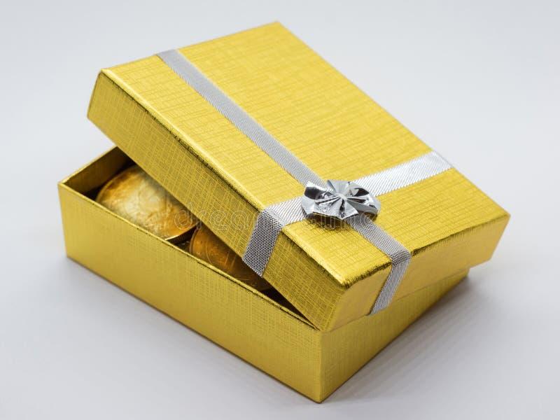 Χρυσό κιβώτιο δώρων με τα χρυσά νομίσματα στοκ εικόνα