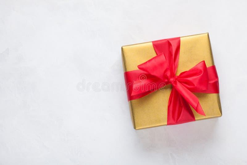 Χρυσό κιβώτιο δώρων που δένεται με μια κόκκινη κορδέλλα που απομονώνεται στο άσπρο υπόβαθρο Τοπ όψη διάστημα αντιγράφων στοκ εικόνες με δικαίωμα ελεύθερης χρήσης