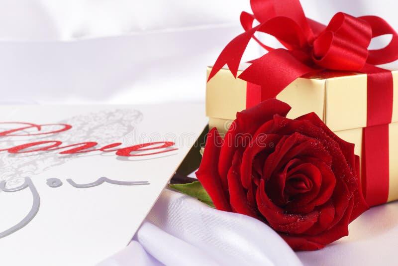 Χρυσό κιβώτιο δώρων και κόκκινα τριαντάφυλλα στο άσπρο υπόβαθρο σατέν στοκ φωτογραφία με δικαίωμα ελεύθερης χρήσης