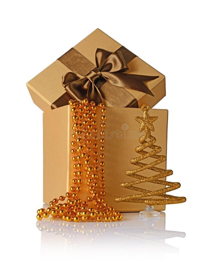 Χρυσό κλασικό κιβώτιο δώρων με το καφετί τόξο σατέν, τη διακοσμημένη με χάντρες γιρλάντα και το ακτινοβολώντας χριστουγεννιάτικο  στοκ εικόνα με δικαίωμα ελεύθερης χρήσης