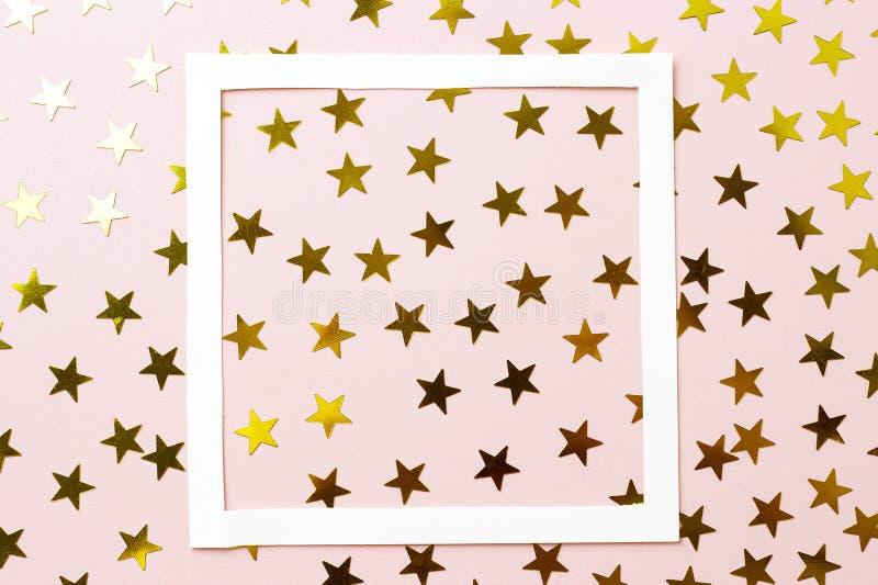 Χρυσό κομφετί και άσπρο πλαίσιο σε ένα ρόδινο υπόβαθρο, τοπ άποψη ελεύθερη απεικόνιση δικαιώματος