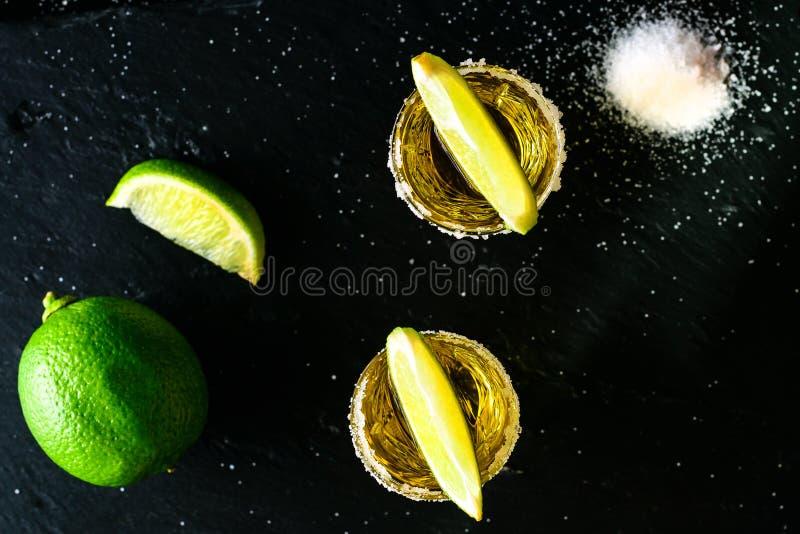 Χρυσό μεξικάνικο tequila με τον ασβέστη και άλας στο σκοτεινό πίνακα τοπ άποψη, στοκ εικόνες με δικαίωμα ελεύθερης χρήσης