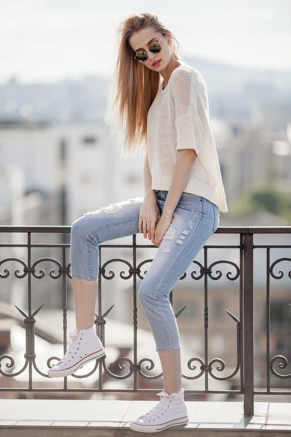 χρυσό μοντέλο μόδας φορεμ Το καλοκαίρι κοιτάζει Τζιν, πουλόβερ, γυαλιά ηλίου στοκ εικόνες με δικαίωμα ελεύθερης χρήσης