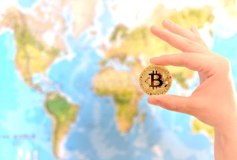 Χρυσό νόμισμα εκμετάλλευσης χεριών Bitcoin ενάντια στο χάρτη του κόσμου Bitcoin στοκ εικόνες