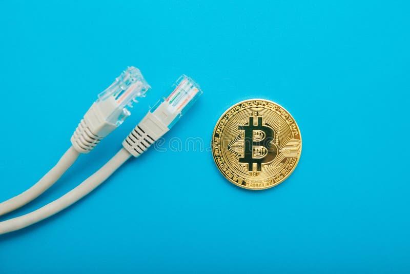 Χρυσό νόμισμα bitcoin με τα καλώδια Διαδικτύου σε ένα μπλε υπόβαθρο στοκ εικόνες