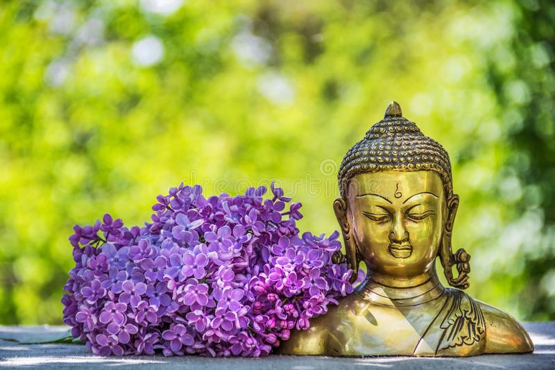 Χρυσό παλαιό άγαλμα του Βούδα Άγαλμα του Βούδα και ανθίζοντας ιώδες κεφάλι του Βούδα στοκ φωτογραφίες
