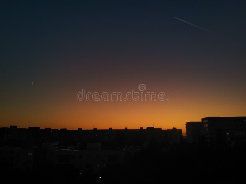 Χρυσό πορτοκαλί ηλιοβασίλεμα πίσω από τη σιλουέτα των ζωντανών μπλοκ, πλανητικό μονοπάτι στα δεξιά και νέο φεγγάρι που λάμπει στα στοκ εικόνες με δικαίωμα ελεύθερης χρήσης