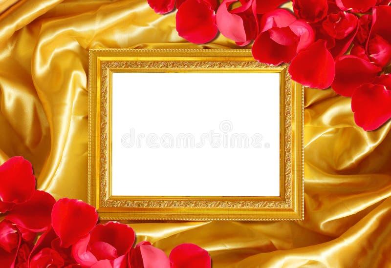 Χρυσό πλαίσιο στο μετάξι υφάσματος με το πέταλο τριαντάφυλλων στοκ εικόνα