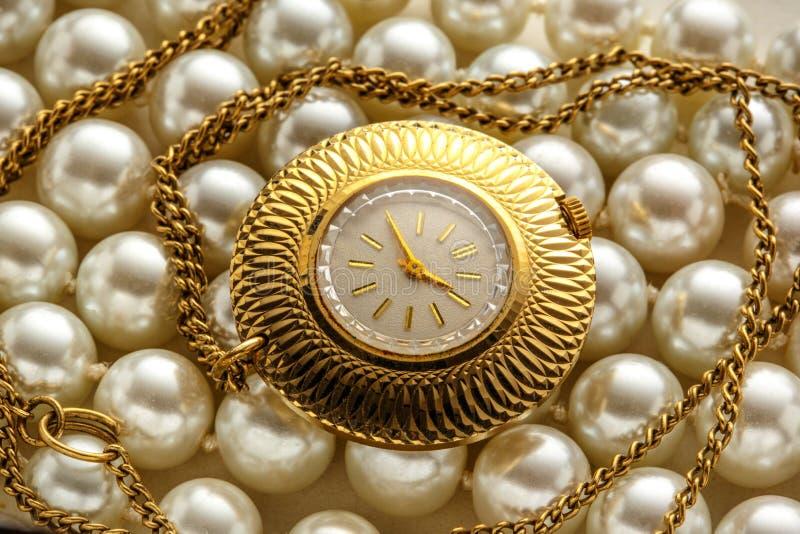 Χρυσό ρολόι στην κινηματογράφηση σε πρώτο πλάνο στο μαργαριτάρι στοκ εικόνα