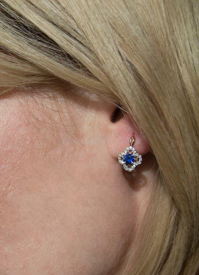 Χρυσό σκουλαρίκι με το σκούρο μπλε πολύτιμο λίθο - σάπφειρος και λίγα διαμάντια μέσα στοκ φωτογραφίες με δικαίωμα ελεύθερης χρήσης