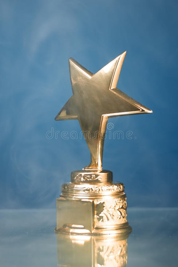 Χρυσό τρόπαιο αστεριών στον καπνό, μπλε υπόβαθρο στοκ φωτογραφία με δικαίωμα ελεύθερης χρήσης