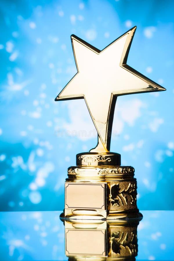 Χρυσό τρόπαιο βραβείων αστεριών στο μπλε κλίμα στοκ εικόνα με δικαίωμα ελεύθερης χρήσης