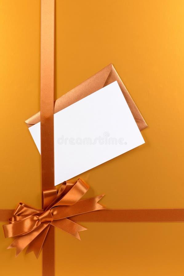 Χρυσό τόξο κορδελλών υποβάθρου δώρων Χριστουγέννων, ετικέττα δώρων ή κάρτα Χριστουγέννων και φάκελος, κάθετη στοκ φωτογραφίες