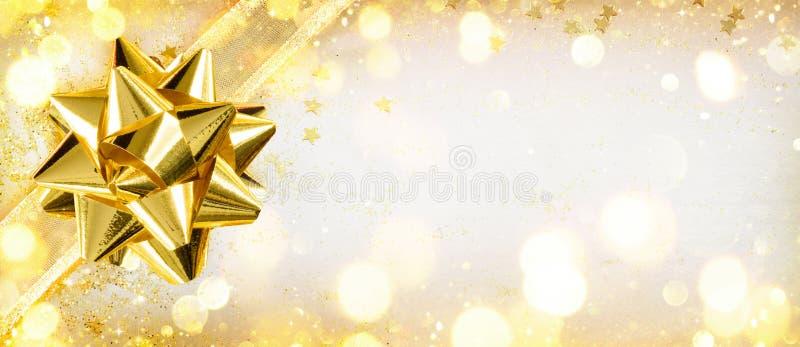 Χρυσό τόξο σε λαμπρό χαρτί δώρων στοκ εικόνες με δικαίωμα ελεύθερης χρήσης