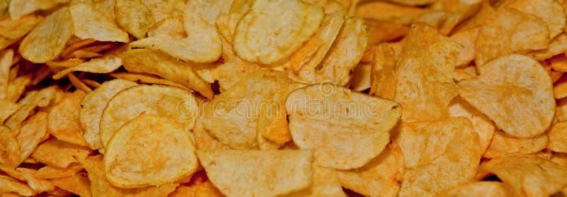 Χρυσό υπόβαθρο τσιπ πατατών η ανασκόπηση πελεκά στενό εκλεκτικό επάνω πατατών εικόνας εστίασης στοκ εικόνα με δικαίωμα ελεύθερης χρήσης