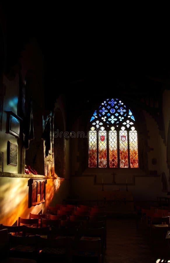 Χρυσό φως του ήλιου μέσω ενός λεκιασμένου παραθύρου γυαλιού που αφορά τον τοίχο μέσα σε μια εκκλησία στοκ εικόνες