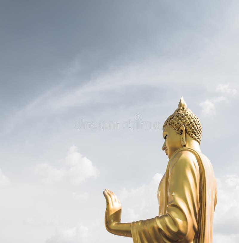 Χρυσό χέρι του Βούδα «στο Ο Κ «σημάδι (ειρήνη) με το μπλε ουρανό και το clou στοκ φωτογραφία με δικαίωμα ελεύθερης χρήσης