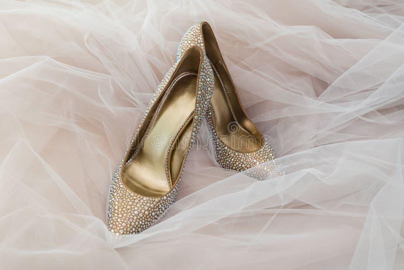 Χρυσό χρώμα νυφών γαμήλιων παπουτσιών με τις πέτρες στο υπόβαθρο του γάμου Tulle στοκ φωτογραφία με δικαίωμα ελεύθερης χρήσης