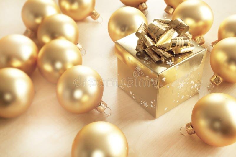 Χρυσό δώρο Χριστουγέννων στο φυσικό υπόβαθρο στοκ εικόνες