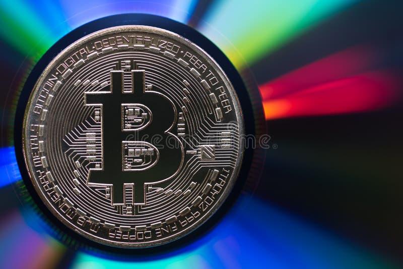 Χρυσό bitcoin σε μια αντανακλαστική ιριδίζουσα πολύχρωμη επιφάνεια στοκ εικόνα