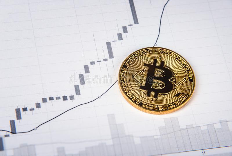 Χρυσό bitcoin στη γραφική παράσταση εγγράφου στοκ φωτογραφίες