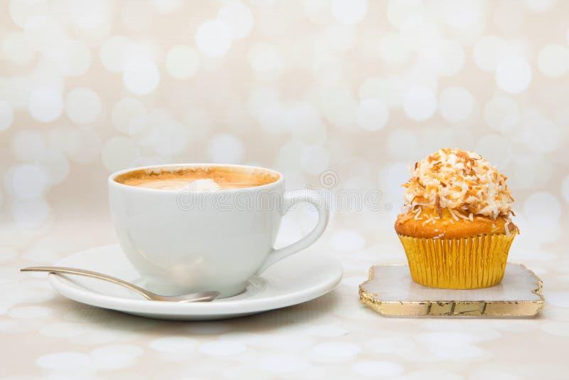 Χρυσό cupcake με το λούστρο καρύδων στην κορυφή και Cappucino στοκ εικόνες